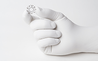 Implant held with thumb and pointer finger