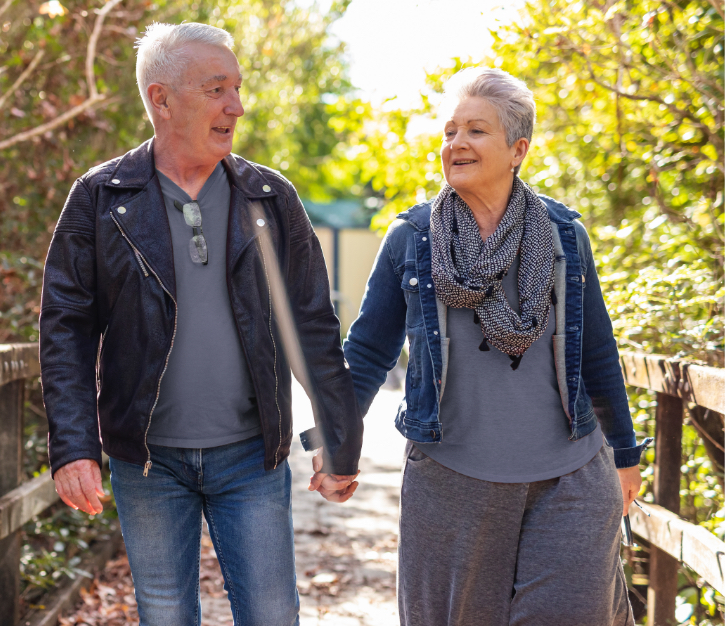 two elderly people holding hands and enjoying a walk